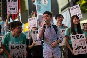 Newly elected legislator Nathan Law thanks supporters during a rally at Causeway Bay.