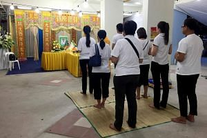 Family members of Mr Lim Sia Thian participating in Buddhist rites at his wake.