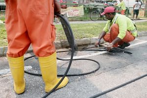 Workers wash the drains by the road along Sims Place.