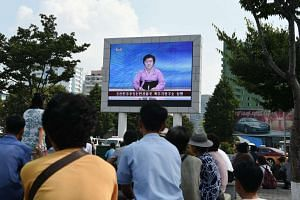 Residents look up at a big screen TV in front of Pyongyang railway station showing television presenter Ri Chun Hee officially announcing that the country successfully tested a nuclear warhead earlier in the day on Sept 9, 2016.