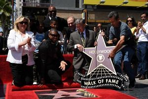 Usher (centre) looks on as his star is unveiled at the Hollywood Walk of Fame in Los Angeles, California, on Sept 7, 2016.