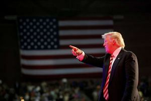 Donald Trump is illuminated by a spotlight as he points to supporters in the crowd after speaking at a campaign rally in Pensacola, Florida, US, on Sept 9.