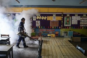A worker fumigating a classroom in Kuala Lumpur last Sunday. On Sept 1, Malaysia reported its first Zika case - a woman who had visited Singapore.