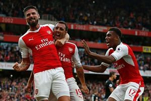 Arsenal's Spanish midfielder Santi Cazorla (centre) celebrates with team-mates after scoring the winning goal from the penalty spot.