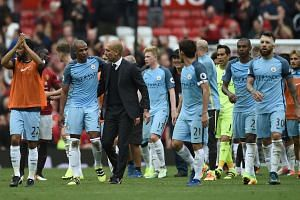 Manchester City's Spanish manager Pep Guardiola and his players celebrate on the pitch after the match.