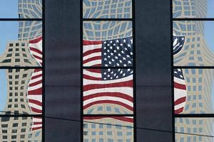 A file picture dated Sept 10, 2003 shows a giant American flag being reflected in the glass of the Century 21 Building which sits opposite of Ground Zero, during preparations for the second anniversary in New York, US.