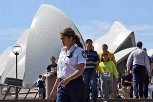 A security guard patrols the forecourt of the Sydney Opera House on Sept 9, 2016, after an 18-year-old man was charged after allegedly making threats at the Sydney Opera House.