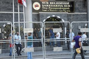 People walk next to barriers in front of the Sur municipality building during a police operation on Sept 11, 2016, in Diyarbakir.