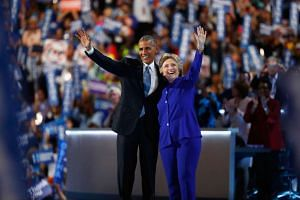 US President Barack Obama and Democratic presidential nominee Hillary Clinton acknowledge the crowd on the third day of the Democratic National Convention at the Wells Fargo Center, on July 27.