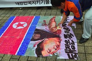 A South Korean activist tears on an caricature picture of North Korean leader Kim Jong Un during a protest denouncing North Korea's latest nuclear test in Seoul on Sept 12, 2016.