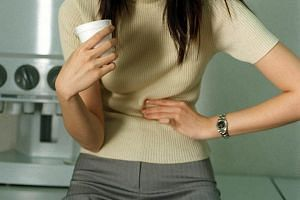 Posed photo of a woman holding her stomach in pain.