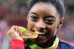US gymnast Simone Biles celebrates with her Olympic gold medal after the women's individual all-around final.