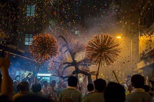 """Members of the fire dragon dance team holding up the """"dragon"""" during the Tai Hang Fire Dragon Dance in Hong Kong on Sept 14, 2016."""