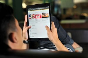 Posed photograph of a man looking at the Singapore Pools website on a tablet.