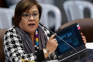 Ms de Lima showing an image of a crime scene at the hearing on killings of drug suspects in the Philippine Senate last week. Yesterday, she was accused of trying to destroy President Rodrigo Duterte.