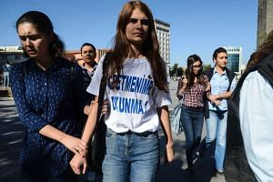 Turkish police detain a student wearing a T-shirt reading