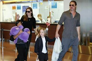 Brad Pitt and Angelina Jolie arrive at Tokyo International Airport with their children Pax Thien (left), Shiloh (hidden) and Knox on July 28, 2013.