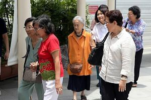 Madam Chung Khin Chun (in orange top) leaving the State Courts with her relative and friends after a hearing earlier this month.