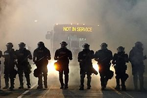 Police officers wearing riot gear blocking a road during protests on Tuesday night after a police officer fatally shot Mr Keith Lamont Scott in the carpark of an apartment complex in Charlotte, North Carolina. Several hundred people gathered to conde