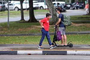 A pedestrian walking past a man travelling on e-scooter on the pavement at Pasir Ris Drive 1 on Sept 21, 2016.