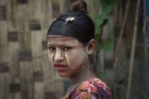 A minority Muslim Rohingya woman wearing traditional facial paste is seen at the Thet Kal Pyin displacement camp in Sittwe on Sept 7, 2016.