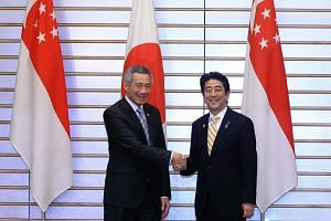 Prime Minister Lee Hsien Loong (left) shaking hands with his Japanese counterpart Shinzo Abe on Dec 13, 2013. PM Lee will be hosted to lunch on Tuesday by Japan's Emperor Akihito and Empress Michiko.