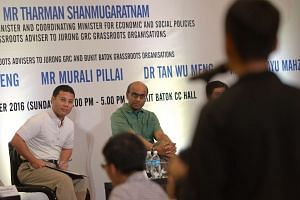 Senior Minister of State Desmond Lim and DPM Tharman listening to a question posed during the dialogue session.