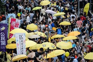 Activists hold yellow umbrellas as they observe three minutes of silence to mark the moment tear gas was used by police on the same day in 2014, in front of the government headquarters in Hong Kong on Sept 28, 2016.