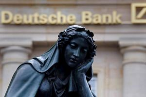 A statue is seen next to the logo of Germany's Deutsche Bank in Frankfurt, Germany.