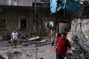 Medics inspect the damage outside a field hospital after an airstrike in Aleppo, Syria, Sept 28, 2016.