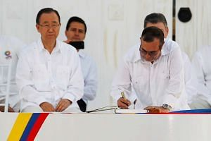 Marxist rebel leader Rodrigo Londono (right) signs an accord ending a half-century war that killed a quarter of a million people in Cartagena, Colombia on Sept 26, 2016.