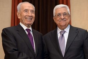 Palestinian President Mahmoud Abbas (right) and former Israeli president Shimon Peres shake hands as they meet at the World Economic Forum in Jordan in 2013.