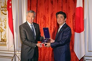 PM Lee receiving the Grand Cordon of the Order of Paulownia Flowers, on behalf of the late Mr Lee Kuan Yew, from Mr Abe in Tokyo yesterday.