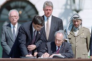 A 1993 file photo  shows  Peres (centre) signing the historic Israel-PLO Oslo Accords on Palestinian autonomy in the occupied territories in a ceremony at the White House, watched by (from left) Israeli Prime Minister Yitzhak Rabin, an unidentified a