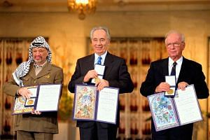 (From left) Palestinian leader Yasser Arafat, Israeli Foreign Minister Shimon Peres and Israeli Prime Minister Yitzhak Rabin with their Nobel Peace Prizes in 1994. PHOTO: EUROPEAN PRESSPHOTO AGENCY