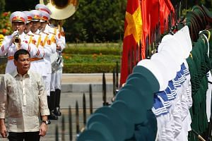 Philippine President Rodrigo Duterte reviewing a guard of honour during a welcoming ceremony at the Presidential Palace in Hanoi yesterday. His aides told reporters that he and Vietnamese President Tran Dai Quang discussed the South China Sea dispute