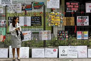 A Filipino student in front of placards at her school during a protest against drug-related killings in Manila yesterday. More than 3,000 people have been killed in a crackdown over the past three months.