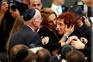 Tsvia, the daughter of former Israeli President Shimon Peres is comforted by her family as she mourns during her father's funeral ceremony.
