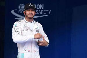 British driver Lewis Hamilton smiles as he celebrates taking pole position.