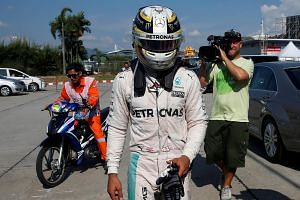 Mercedes' Lewis Hamilton of Britain returns to the paddock after his car caught fire during the 2016 Malaysia Grand Prix on Oct 2, 2016.