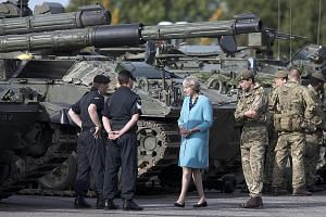 Mrs May visiting a military base in the Salisbury Plain area in England. She faces her first party conference as leader today, amid concerns over the economic fallout over Brexit and the Conservative Party's unity on the issue.
