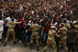 Demonstrators chant slogans while flashing the Oromo protest gesture during Irreecha, the thanksgiving festival of the Oromo people, in Bishoftu town, Ethiopia on Oct 2, 2016.