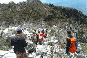 Rescuers taking Mr Woon Tai Kiang's body down Mount Kinabalu yesterday. He is believed to have fallen about 150m into a ravine after slipping off the trail, and died of serious head injuries, according to rescuers and police. Mr Woon was an avid and