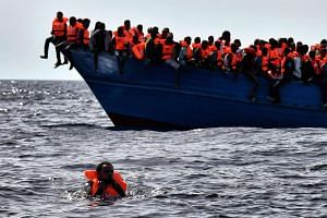Migrants wait to be rescued as they drift in the Mediterranean Sea some 20 nautical miles north off the coast of Libya on Oct 3, 2016.