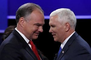 Mr Tim Kaine (left) and Mr Mike Pence pass each other on stage after their televised debate.