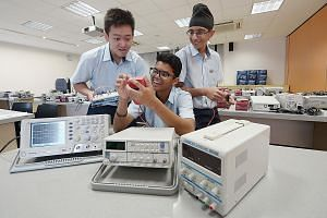 From left: Hong Kah Secondary students Juan Sebastian, Abdul Hafiz Abdul Hamid and Alwinderjit Singh Basant at an electronics lab. The school offers an elective in fundamentals of electronics in partnership with Ngee Ann Polytechnic.
