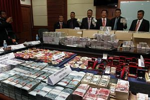 Datuk Azam (third from right) and other officers showing cash and jewellery seized from the top two officials of the Sabah Water Department in Kota Kinabalu on Wednesday.