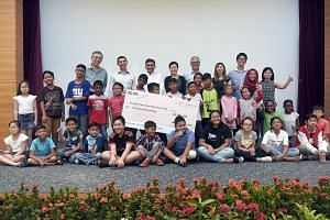 Beneficiaries of The Straits Times School Pocket Money Fund with a cheque for a $500,000 donation to the fund at an Appreciation Day event yesterday. With them are (from back row, left) fund trustee Sia Cheong Yew; fund chairman and ST editor Warren