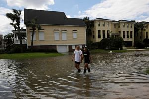 People walk through flooded streets after Hurricane Matthew hit, In Jacksonville Beach, Florida, Oct 8, 2016.