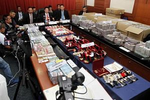 The cash and jewellery seized during the raid on the two senior officials' homes.